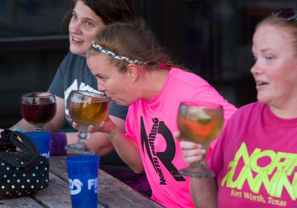 From left: Hannah Rupley, Julie Vinson and Charity Dragna, members of the North Running Crew, have a beer at Fred's after their 5K run along Western Center Road in north Fort Worth. (Robert W. Hart/Special Contributor)