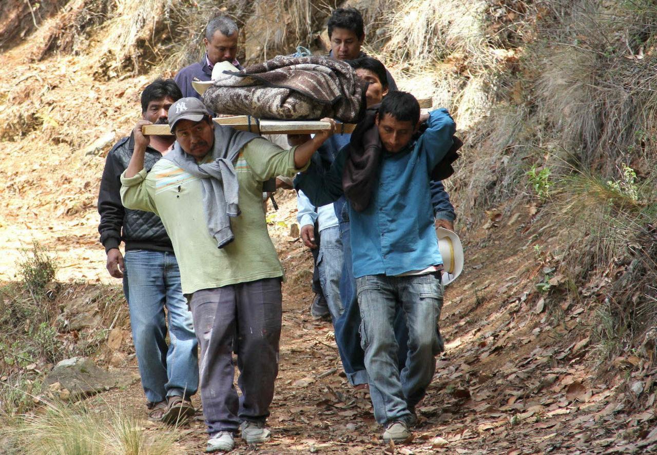 Residentes de El Mirador, en Coxcaltlan llevan uno de los 11 miembros de una familia que fueron asesinados. (AFP/GETTY IMAGES/SAÚL MUÑOZ)