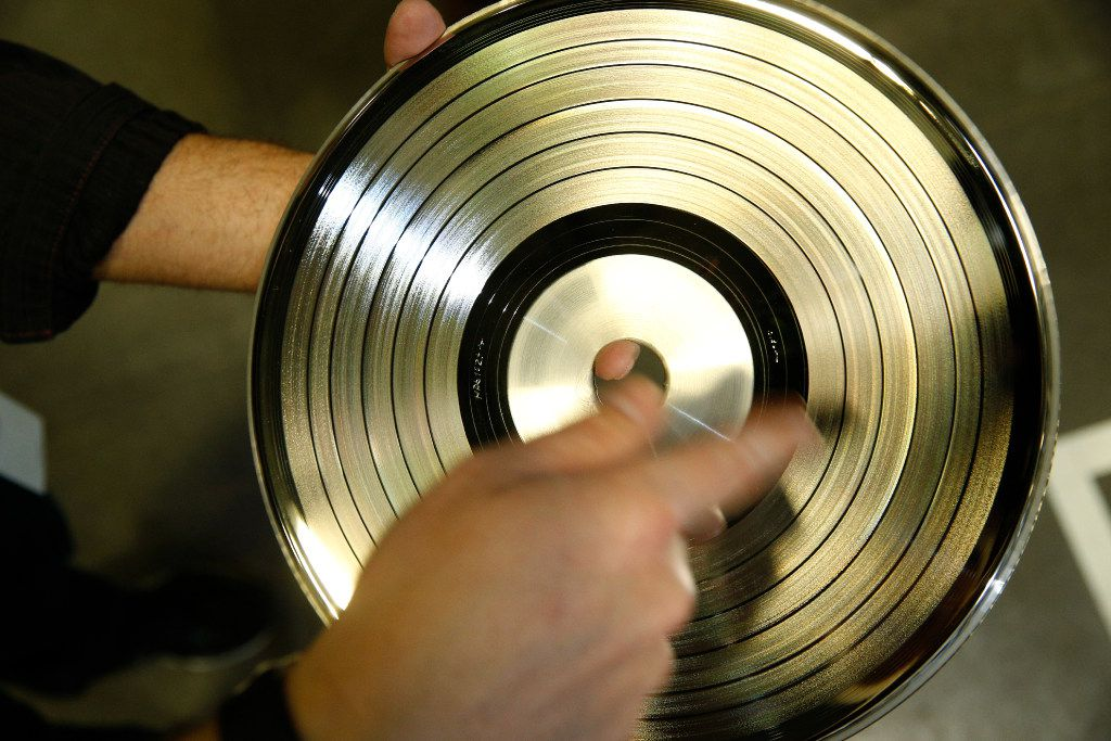 Metal masters, inscribed with sides A and B, are used to press records. The vinyl is flash heated and cooled through a network of water pumps to make the permanent markings.