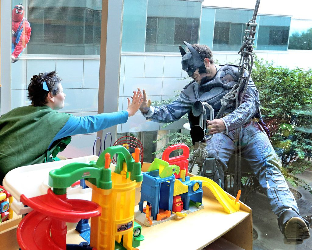 Children's Medical Center Plano patient Ryan Olin, left, reaches out to window washer Joshua Rodriguez, dressed as Batman. (Louis DeLuca/The Dallas Morning News)