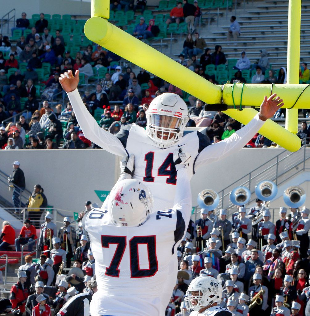 Allen quarterback Grant Tisdale (14) is hoisted in the end zone by teammate Trey Stratford (70) as the two celebrate following his second quarter rushing touchdown in their game against Euless Trinity.The  teams played their Class 6A Division l Region l final football game at The University of North Texas' Apogee Stadium on December 9, 2017. (Steve Hamm/Special Contributor)