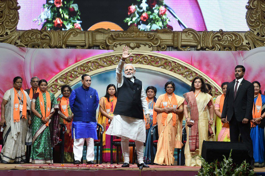 Indian Prime Minister Narendra Modi (C) waves on stage during the Bhartiya Janta Party (BJP) Mahila Morcha Sammelan (women convention) in Adalaj, some 30 kms from Ahmedabad on Dec. 22, 2018.