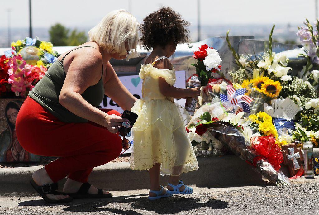 Jessica (izq.) y Kalani Windham dejan flowers, en homenaje a las víctimas, al pie del Walmart donde fue la balacera del sábado en El Paso.
