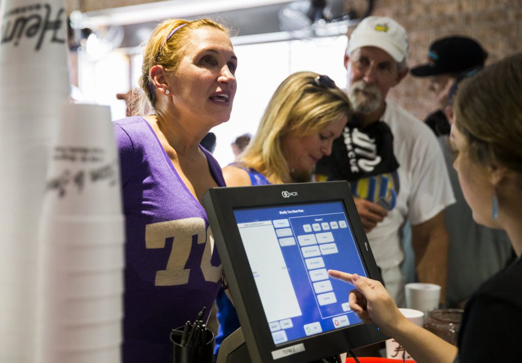 Emily McLaughlin orders at the register as the first customer at Heim Barbecue's new location on Saturday, August 6, 2016 on W. Magnolia Ave. in Fort Worth. McLaughlin, Cindy Podner (center) and Jeff Knipper (right) waited in line over night.