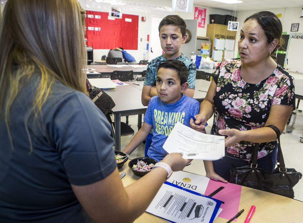 Kassandra Dena (izq), una maestra de ciencias y escritura, entrega unos papeles a Adriana Aguirre y sus hijos Daniel y Miquel, en un evento de apertura de la nueva escuela magnet en Pleasant Grove. (DMN/CARLY GERACI)