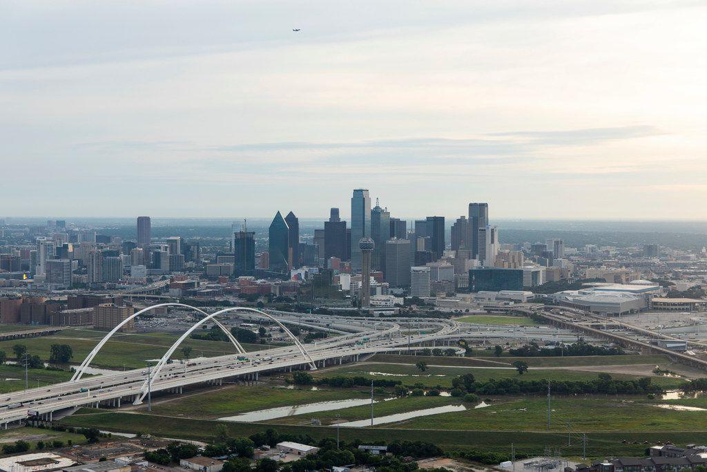 Margaret McDermott Bridge, bottom, seen crossing the Trinity River on I-30 as the sunrises behind the Dallas skyline on Friday, June 14, 2019. (Shaban Athuman/Staff Photographer)