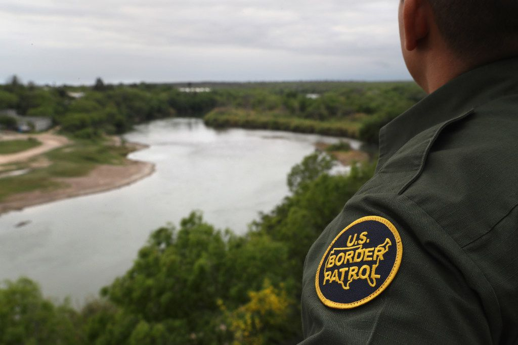 A U.S. Border Patrol agent scans the U.S.-Mexico border from a bluff overlooking the Rio Grande River in Roma, Texas.