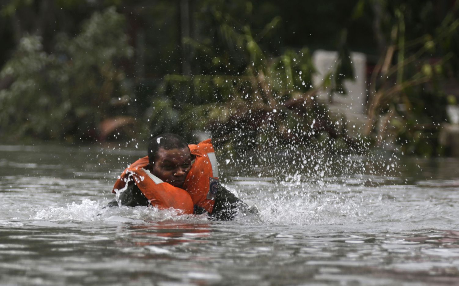 A rescuer falls into a flooded street in Havana, after the passing of Hurricane Irma in Cuba, Sunday, Sept. 10, 2017.