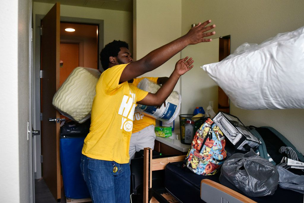 Sophomore Juwon Grant president of the Resident Hall Association  tosses a bag with a pillow as he and other student volunteers helped incoming freshman move into the dorms at the University of North Texas at Dallas.