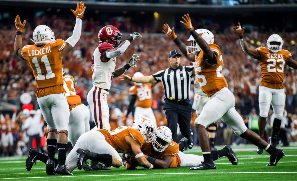 FILE - Texas Longhorns defensive back Brandon Jones (19) and defensive back Kris Boyd (2) recover a fumbled ball by Oklahoma Sooners wide receiver CeeDee Lamb (2) during the fourth quarter of the Big 12 Championship football game between the Texas Longhorns and the Oklahoma Sooners on Saturday, December 1, 2018 at AT&T Stadium in Arlington, Texas. (Ashley Landis/The Dallas Morning News)