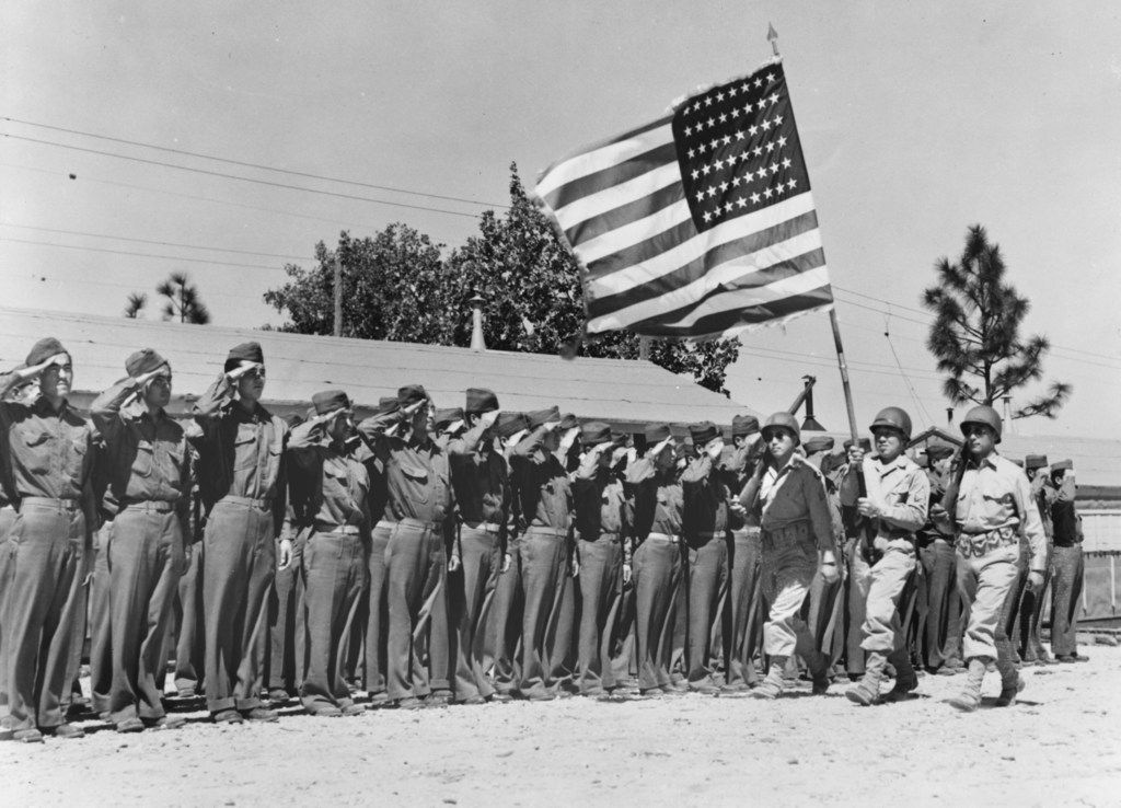"""It's """"Present arms!"""" for members of the 442nd Regimental Combat Team, Japanese-American fighting unit, as they salute their country's flag in a brief review held the day of their arrival at Camp Shelby, Miss."""