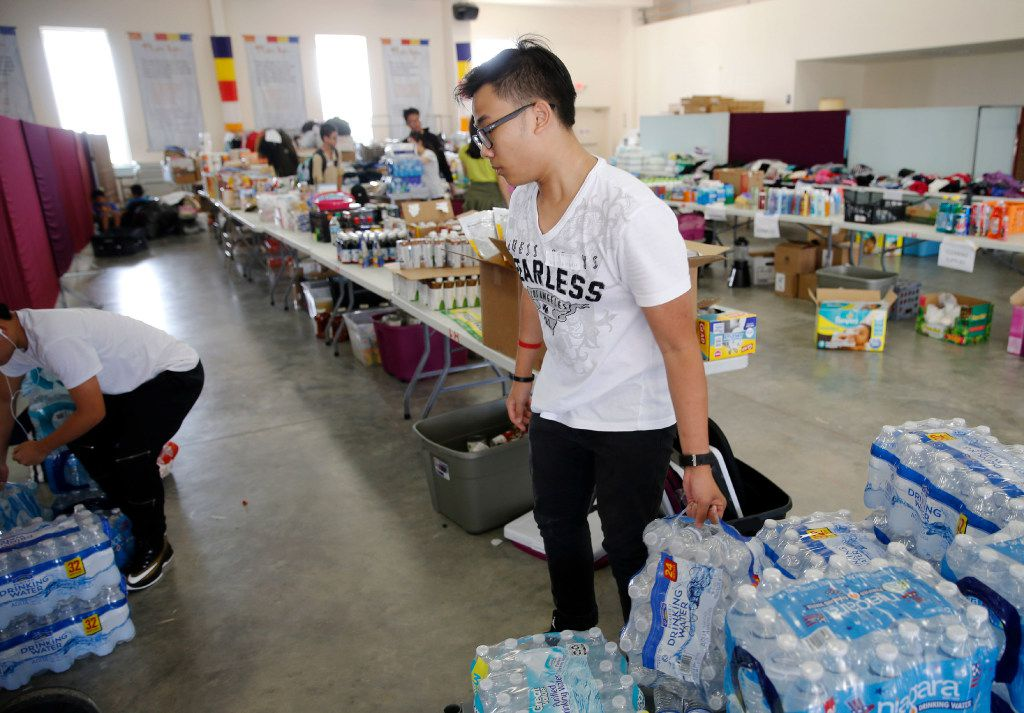 Huy Huynh works on stocking cases of water in a donation area at the Lien Hoa Temple in Houston on Monday.