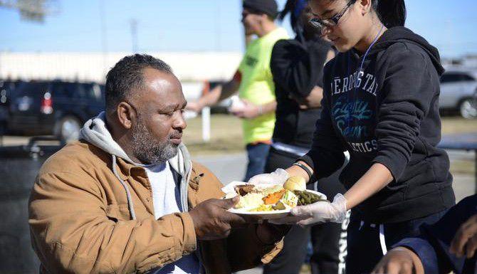 La voluntaria Nancy Morataya, de 13 años, ofrece un plato de comida a Howard B. Bates Sr., en un evento para indigentes. El cabildo de Dallas esta semana relajó las restricciones para ayudar a las personas en las calles. (DMN/ROSE BACA)