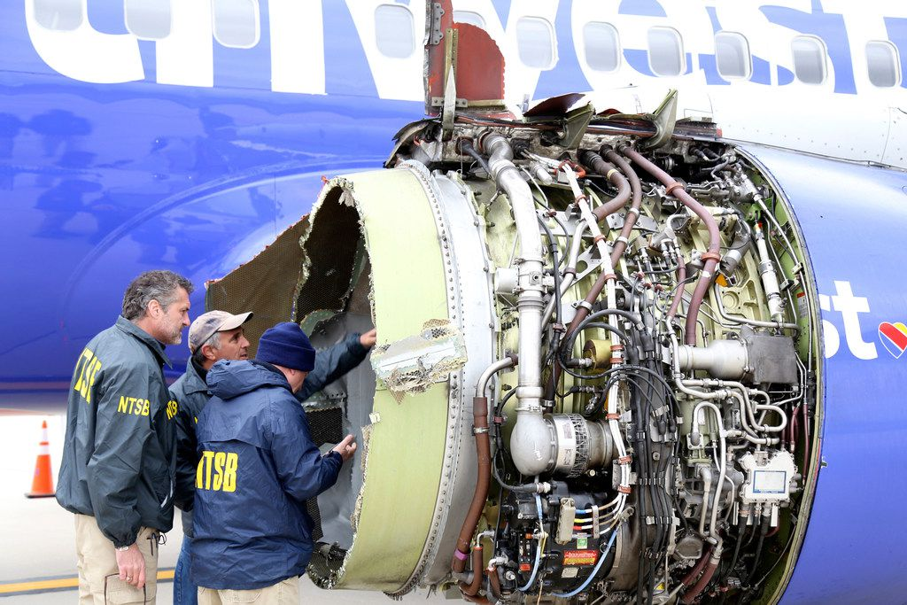 FILE photo shows NTSB investigators examining damage to the engine of the Southwest Airlines flight 1380 plane after an April 17, 2018 engine failure which killed passenger Jennifer Riordan and injured eight others.