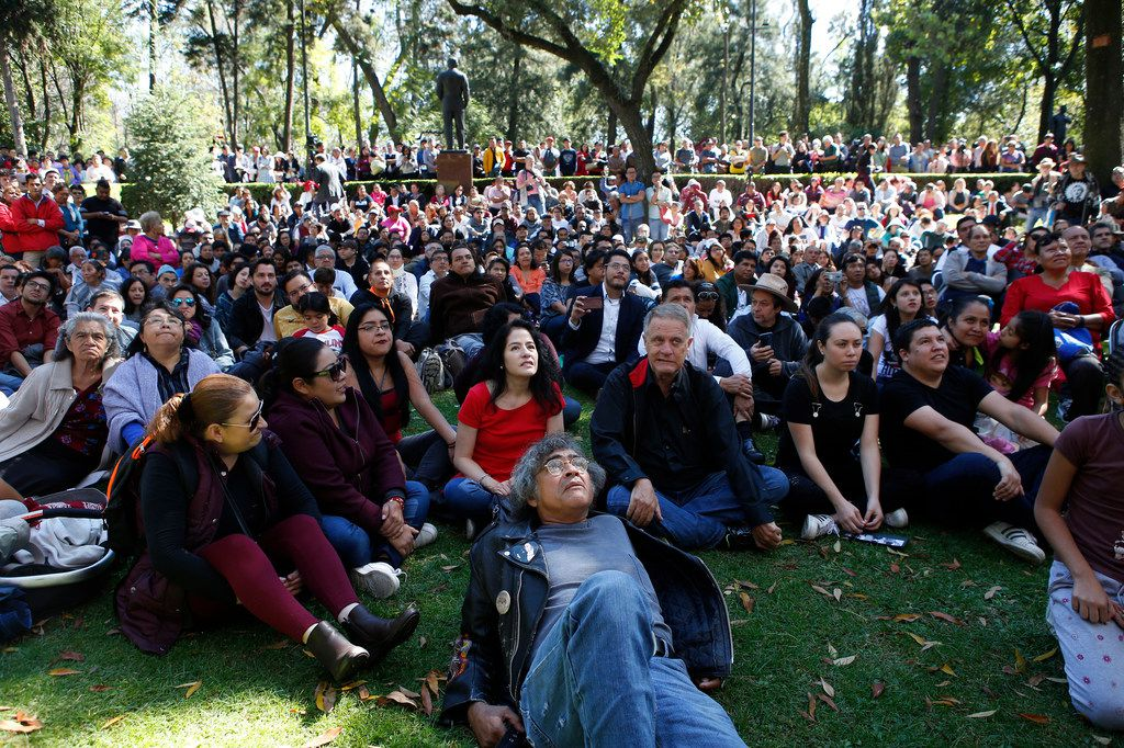 Visitors watch the presidential inauguration ceremony on an outdoor video screen broadcast live, while sitting on the lawn of the Los Pinos presidential residence complex, now open to the public,  in Mexico City, Saturday, Dec. 1, 2018.