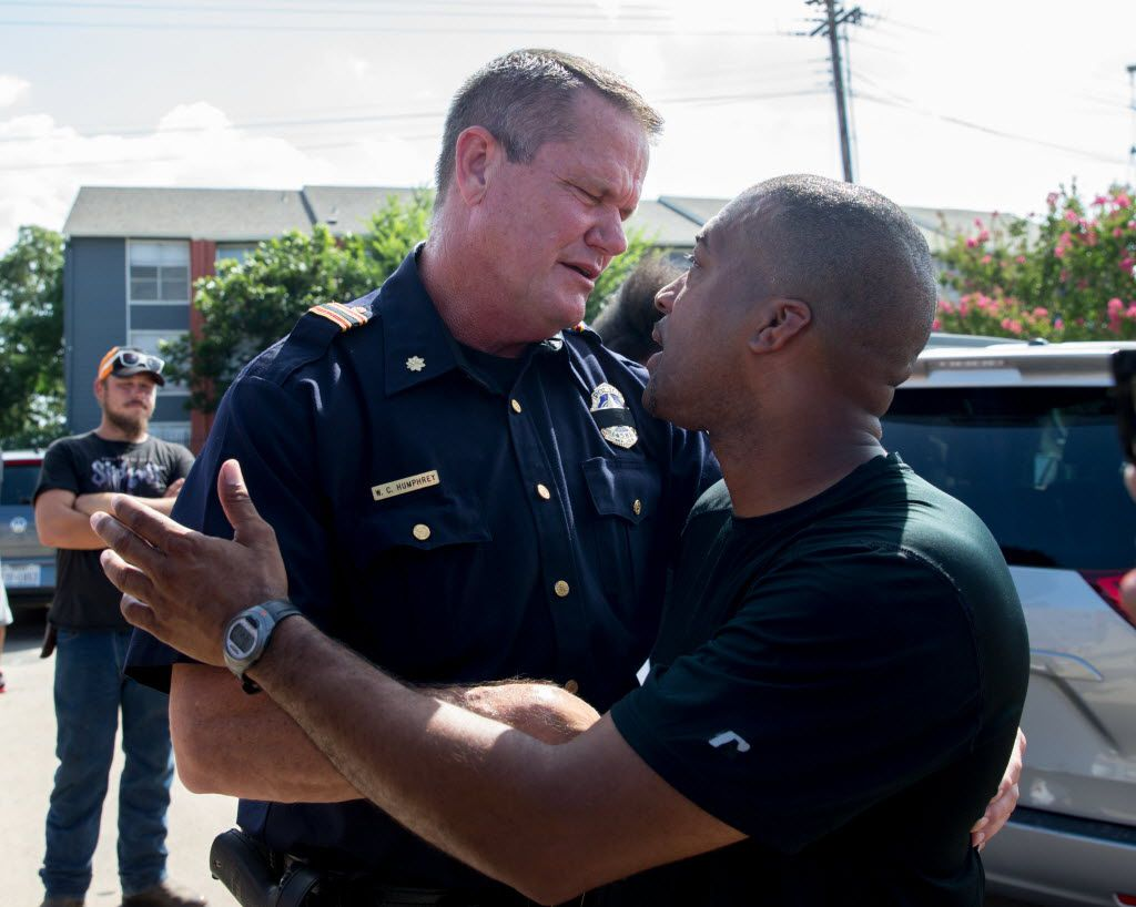 Officer W.C. Humphrey shake hands and embrace with Ty Hardaway, 44, of Dallas during the Black Lives Matter rally at the corner of Park Ln and Ridgecrest Rd on July 10, 2016 in Dallas. (Ting Shen/The Dallas Morning News)