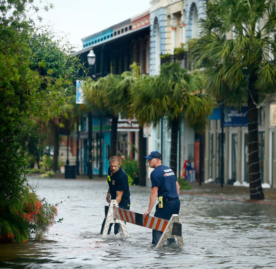 A Galveston and Beaumont firefighter move a traffic barrier in the historic Strand District to let a fire truck pass in Galveston, Texas, August 29, 2017. The city was flooded from punishing overnight rains from Tropical Storm Harvey which passed by the island, Tuesday.  (Tom Fox/The Dallas Morning News)