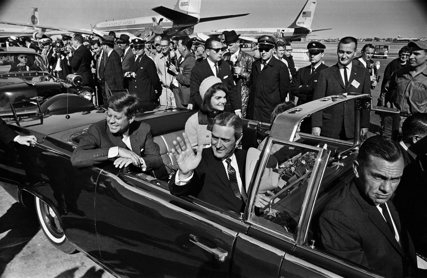 President John F. Kennedy and Jacqueline Kennedy begin the motorcade from Love Field to downtown Dallas on Nov. 22, 1963. Texas Gov. John Connally is waving. (Tom Dillard/The Dallas Morning News)