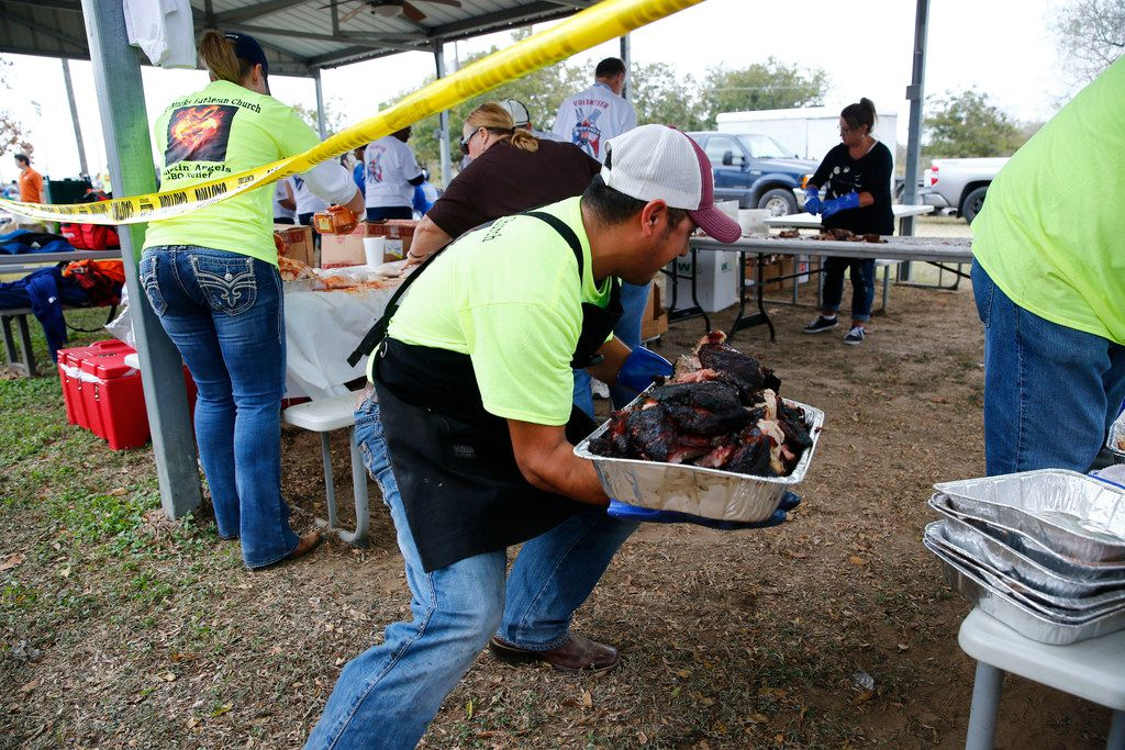 Adam Garcia from San Antonio's Lone Star Grillers moves smoked pork after he cooked it to the cutting tables during Smokin' Angels BBQ Relief in St. Mark's Lutheran Church in Adkins, Texas on Nov. 11, 2017. All proceeds from the event go to the victims of the First Baptist Church in Sutherland Springs, Texas was the site of a shooting that killed 26 parishioners and left 30 injured.