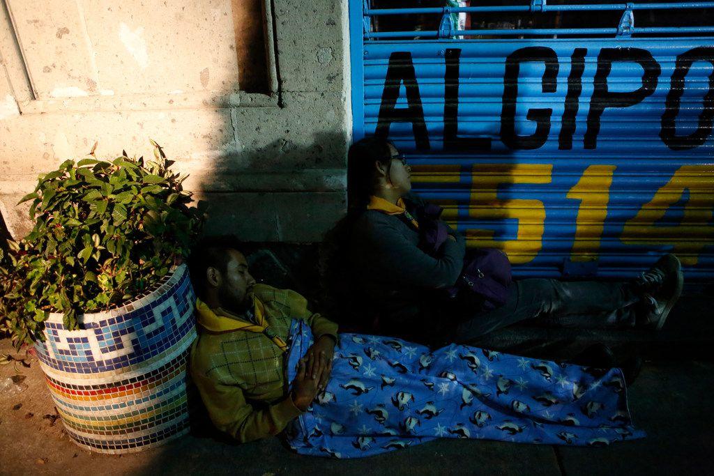 Exhausted family members waiting for news of missing relatives sleep on the sidewalk as rescue workers labor to reach survivors trapped inside a collapsed office building in the Roma Norte neighborhood of Mexico City, in the early morning hours of Saturday, Sept. 23, 2017. A 7.1 magnitude earthquake Tuesday toppled more than three dozen buildings in the capital, leaving at least 46 people believed missing in this office building alone.