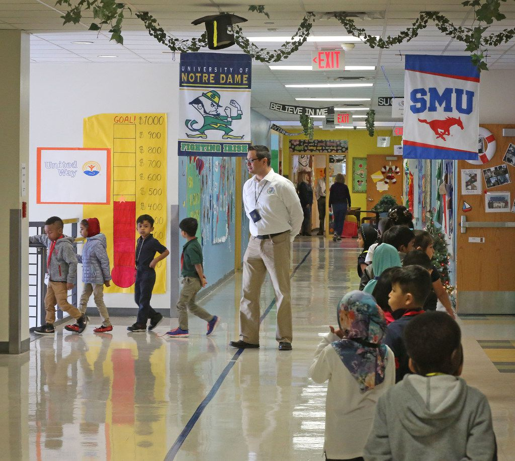 Teacher's assistant Adrian Rivera watches students make their way through the hallways at Dallas ISD's McShan Elementary in Vickery Meadow.