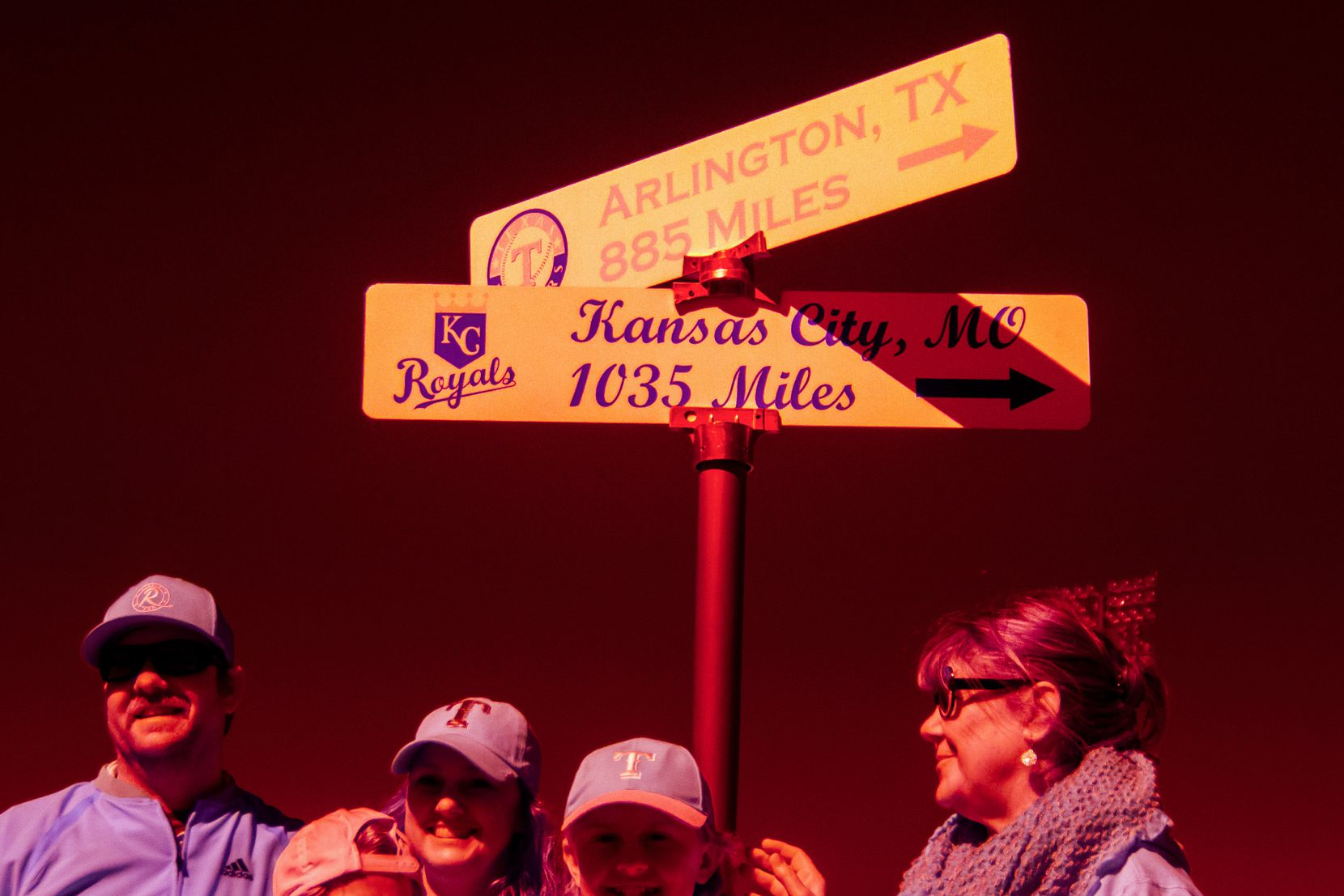 Fans pose for photos near a sign showing the distances to the homes of the Texas Rangers and the Kansas City Royals before a spring training baseball game at Surprise Stadium.