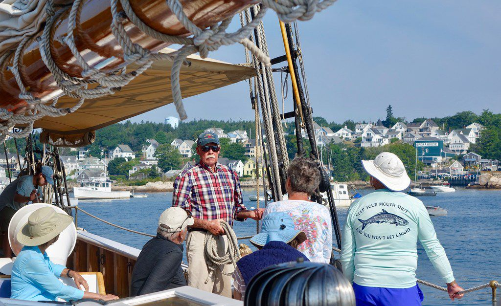 Capt. John Foss (center) explains to passengers how they will climb over the side and down a ladder to the boat they will row to shore in Stonington, Maine.