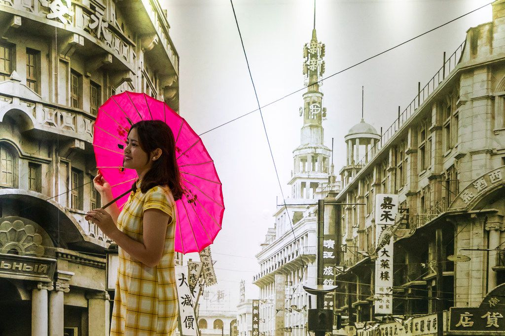 A woman poses in front of a mural made from a historic photo of Shanghai.