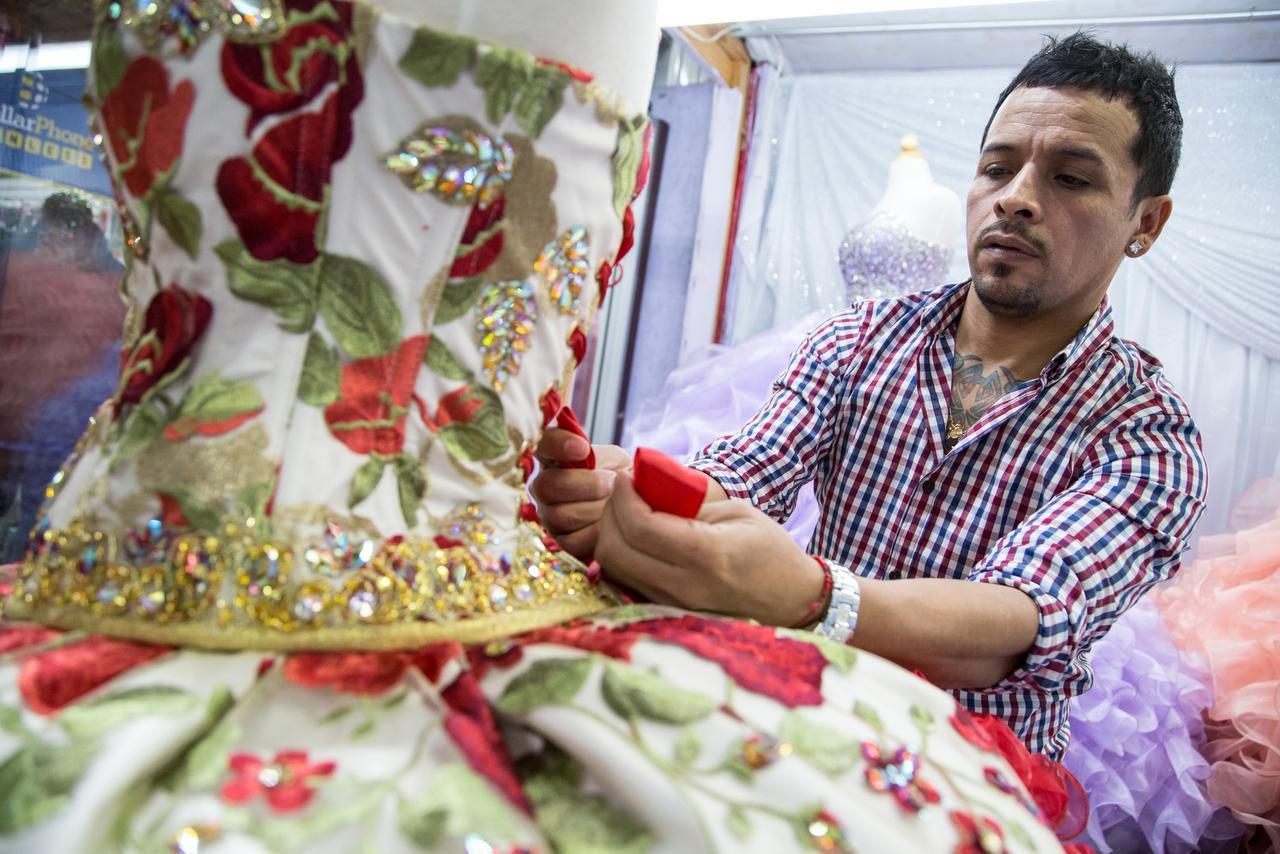 Luis García muestra una réplica del vestido que envió a Rubí, en su tienda del Harry Hines Bazaar. La quinceañera de la joven se volvió viral y el diseñador vio una ventana de oportunidad. (ESPECIAL PARA AL DÍA/MARÍA OLIVAS)