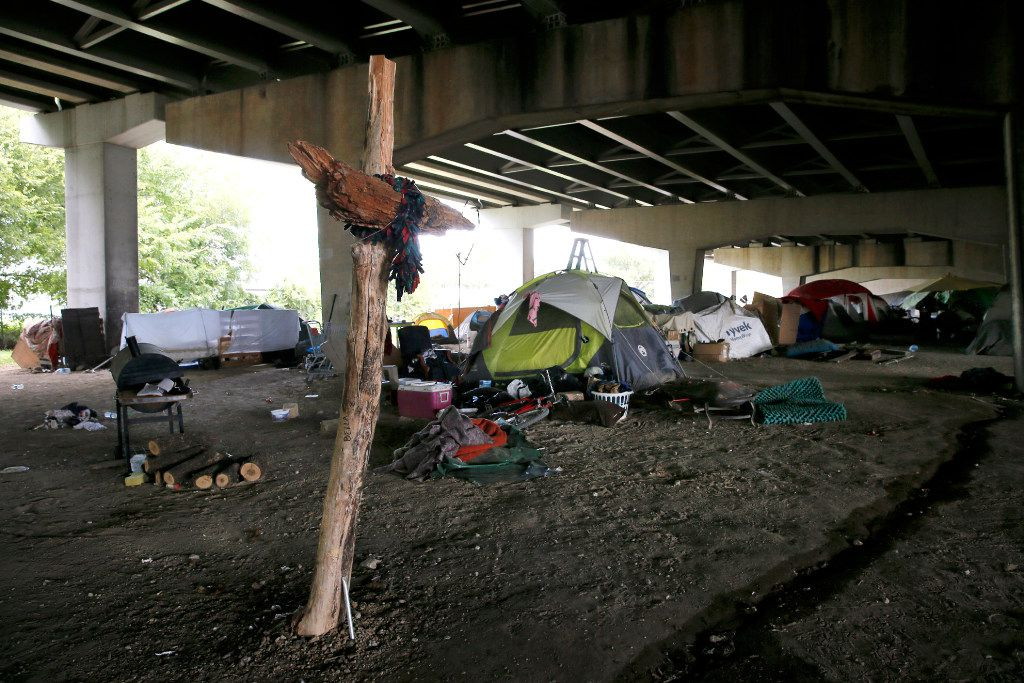 Amid a makeshift cross, homeless residents live in an encampment beneath Interstate 30 near Fair Park.