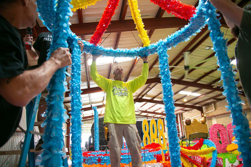 Clyde Watts of Dallas-based Lone Star Parade Floats works on the Whataburger-themed float that was part of the Battle of Flowers Parade during Fiesta San Antonio.