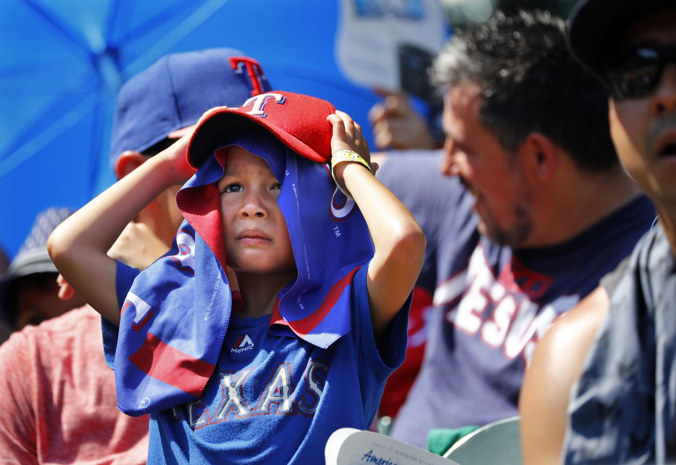 A young Texas Rangers fan takes cover form the searing sun as he watches his team face the Cleveland Indians at Globe Life Park in Arlington, Texas, Sunday, July 22, 2018.  By the end of the game the temperature was 108¼, one of the hottest games on record.
