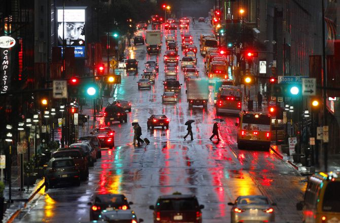 Workers hustle home with umbrellas across Elm Street in downtown Dallas during an evening rush hour.