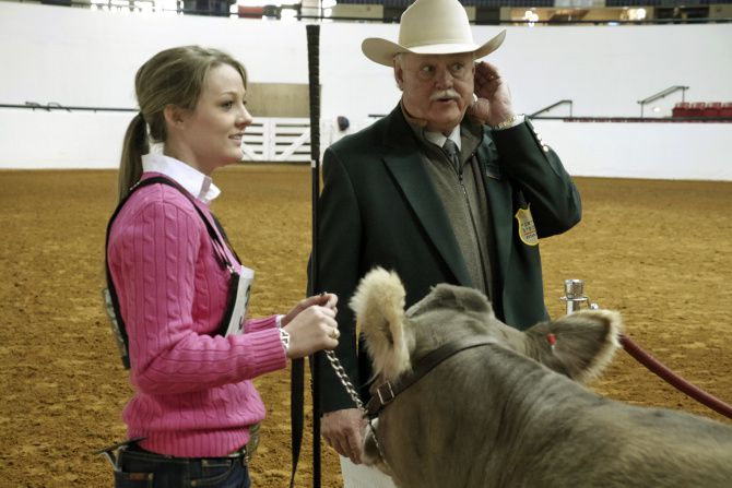 Jessica Johnston with the Broken Oak Ranch out of Seguin and Livestock Superintendent Mike Sands listen to numbers called for the next round at Watt Arena. Johnston won her class with Lola Junior, an 8-month-old heifer.