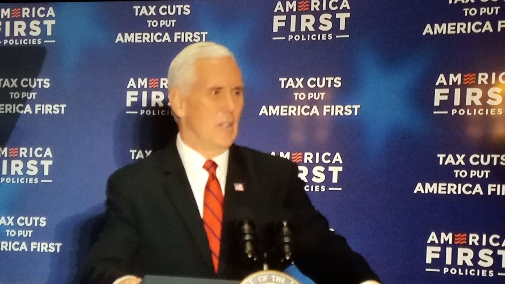 Vice President Mike Pence appears on a TV screen at the Dallas Sheraton on Feb. 17, 2018, for an event focused on the GOP's $1.5 trillion tax revamp.