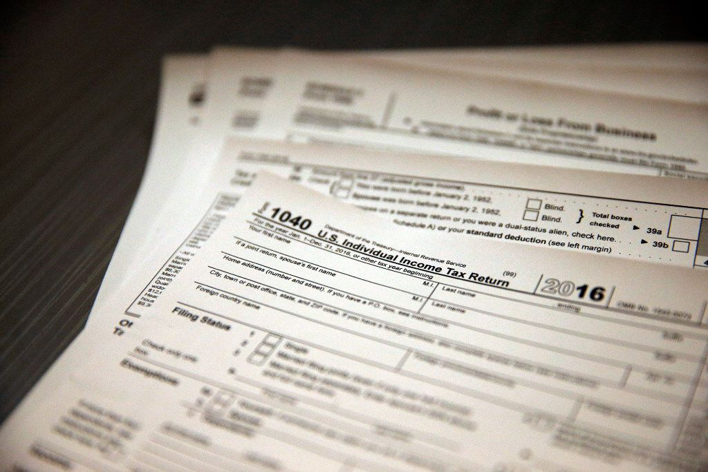 In this Jan. 14, 2017, photo, tax forms sit on a desk. (AP Photo/Brennan Linsley)