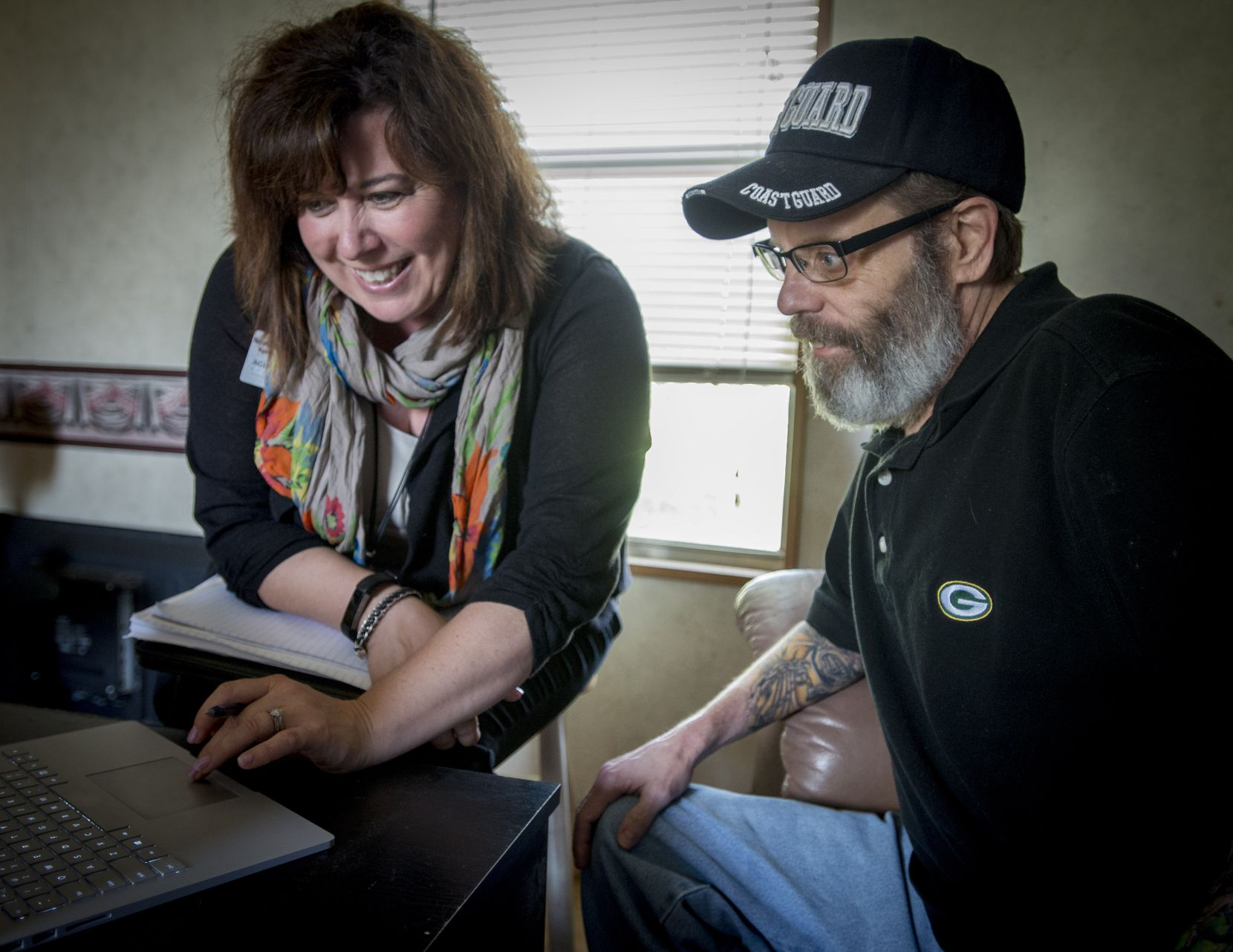 Geriatric care manager Nicole Kulas goes over personal health data with Stephen Kelly in his Roanoke, Texas, home.