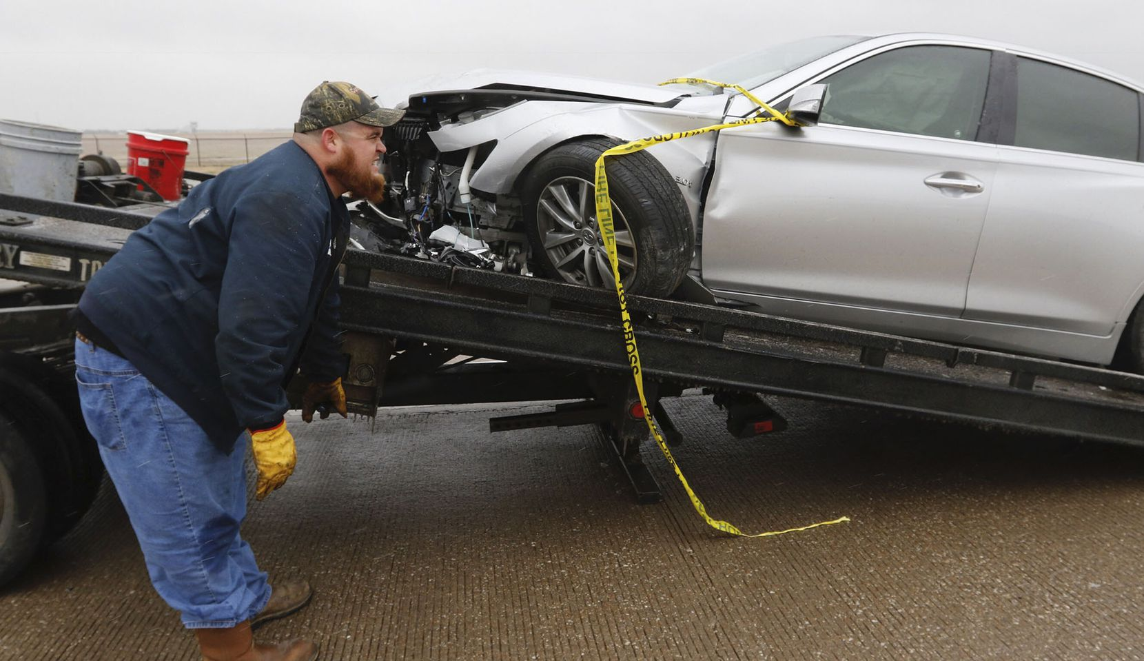 David Messer, of J & S Towing, hooks up a wrecked car on a ice covered Highway 67 at the Hampton Road overpass on Sunday afternoon in Dallas on December 31, 2017. Temperatures were not expected to get out of the 20's on Sunday.