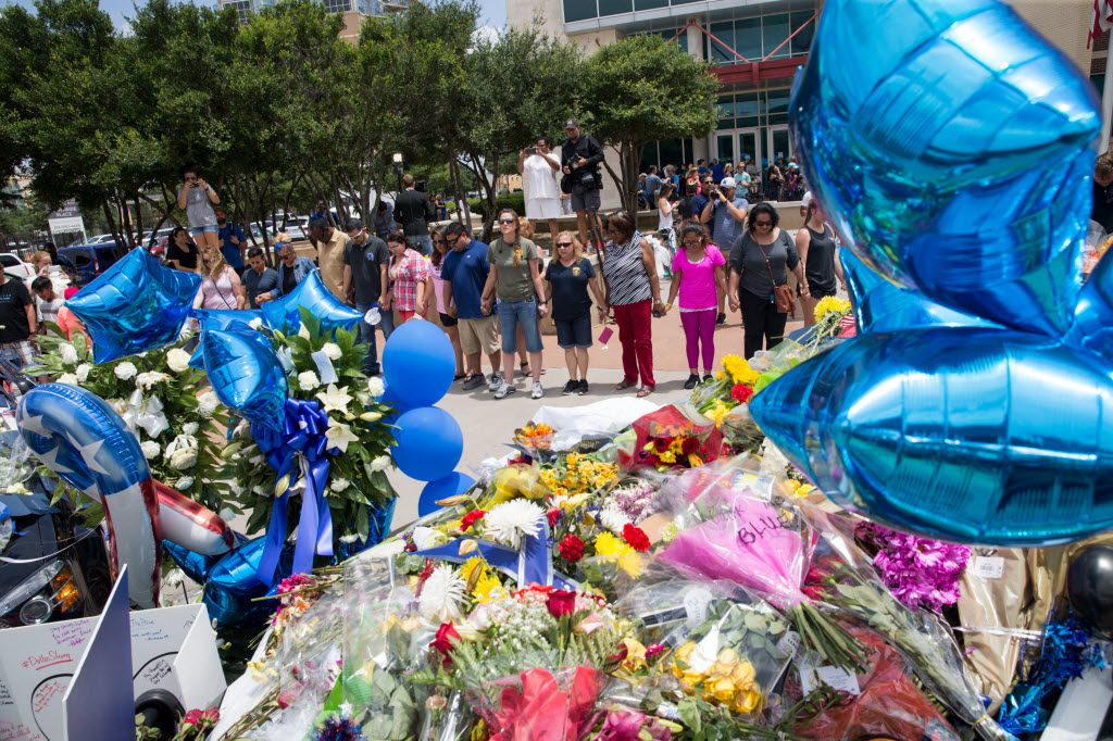 People form a prayer circle surrounding  the memorial for the slain officers at the Dallas Police Headquarters on July 9, 2016 in Dallas. (Ting Shen/The Dallas Morning News)