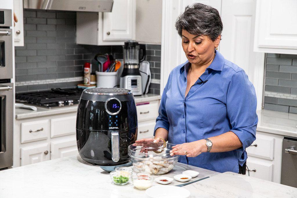 Urvashi Pitre prepares tandoori shrimp in an air fryer at her home in Keller.