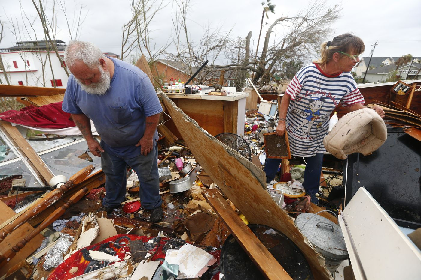 Bill and Paulette Rogers search the second story of their home for his wallet after Hurricane Harvey destroyed their house in Port Aransas, Texas.
