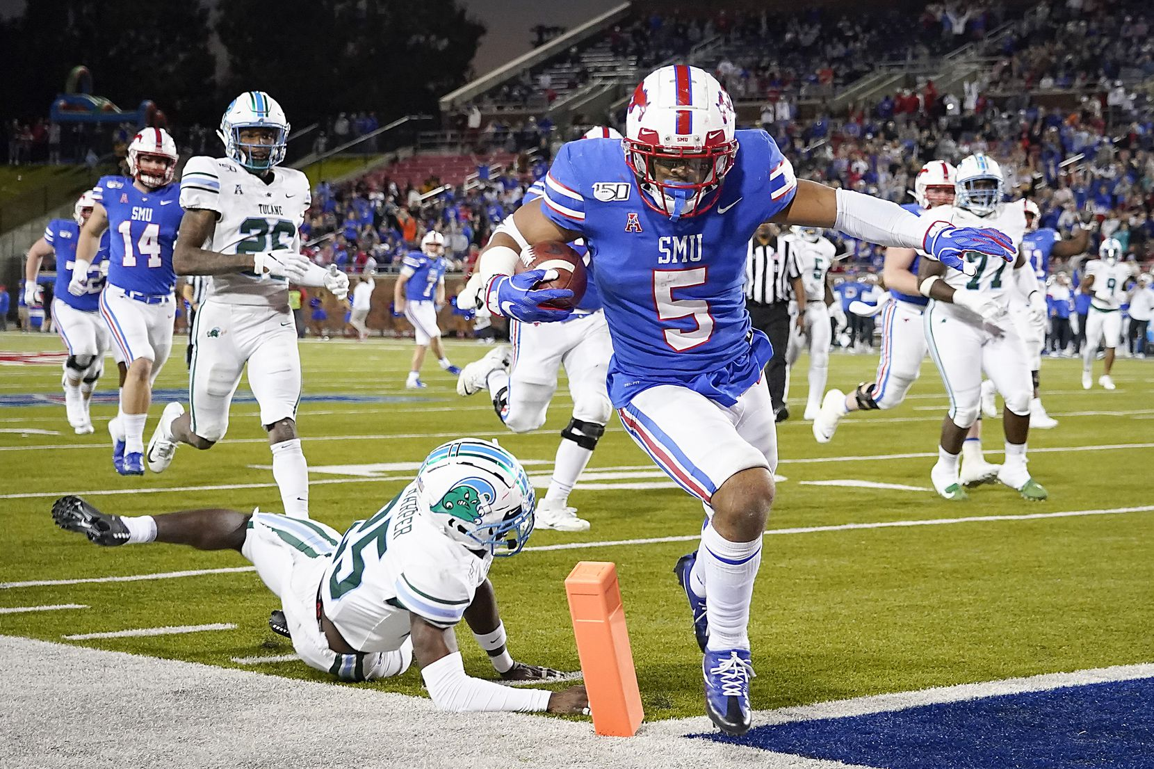 SMU running back Xavier Jones (5) scores on a 25-yard touchdown run past Tulane safety Will Harper (25) during the second half of an NCAA football game at Ford Stadium on Saturday, Nov. 30, 2019, in Dallas. The Mustangs won the game 37-20.