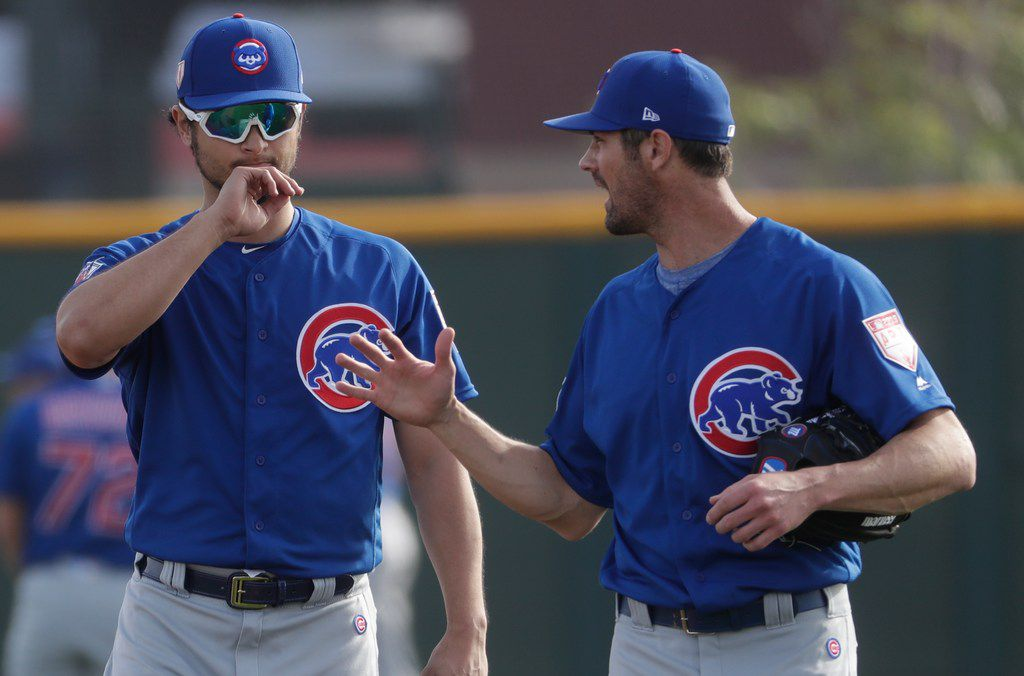 Chicago Cubs' Yu Darvish talks to Cole Hamels during a spring training baseball workout Friday, Feb. 15, 2019, in Mesa, Ariz. (AP Photo/Morry Gash)