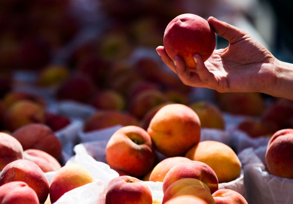 People choose peaches during the Parker County Peach Festival in downtown Weatherford.
