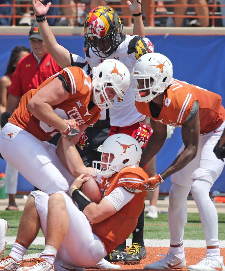 Teammates help Texas Longhorns quarterback Shane Buechele (7) to his feet after a third quarter rushing touchdown during the University of Maryland Terrapins vs. the University of Texas Longhorns NCAA football game at Darrell K Royal Texas Memorial Stadium in Austin, Texas on Saturday, September 2, 2017. (Louis DeLuca/The Dallas Morning News)