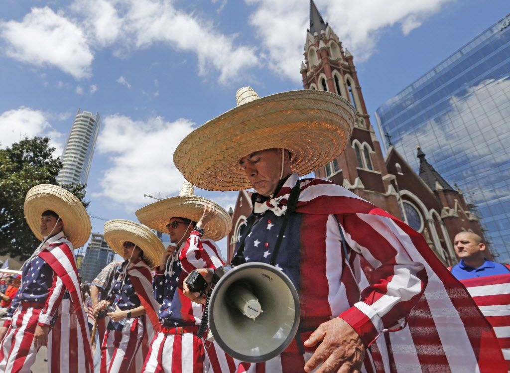The Arellano family heads down Ross Avenue during the Mega March, which started at the Cathedral Shrine of Our Lady Guadalupe in downtown Dallas, photographed on Sunday, April 9, 2017. (Louis DeLuca/The Dallas Morning News)