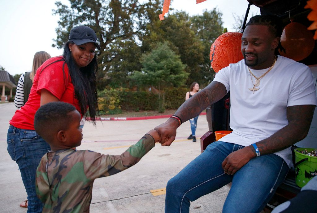 Dallas Cowboys safety Kavon Frazier gives Gage Rodgers, 4 a fist bump as Lola Wilson walks with him during a Trick a Trunk event at Greater Cornerstone Baptist Church in Dallas on Friday, October 20, 2017. Frazier was at his charitable foundation event called Trick a Trunk. It's a safe alternative for trick or treating for families. At the free event, people can win free Dallas Cowboys tickets and a $50 prize for the best decorated trunk. (Vernon Bryant/The Dallas Morning News)