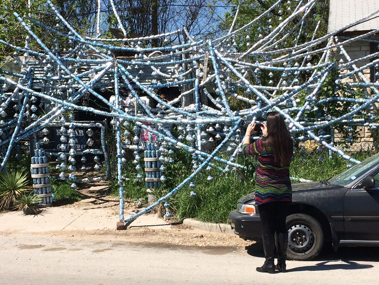 Nadia Martin stops to take a picture of the Beer Can House in Fort Worth.