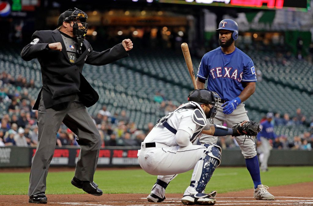 Umpire Tripp Gibson, left, calls out Texas Rangers' Danny Santana, right, on strikes as Seattle Mariners catcher Omar Narvaez lines-up for the next batter in the first inning of a baseball game Thursday, April 25, 2019, in Seattle. (AP Photo/Elaine Thompson)