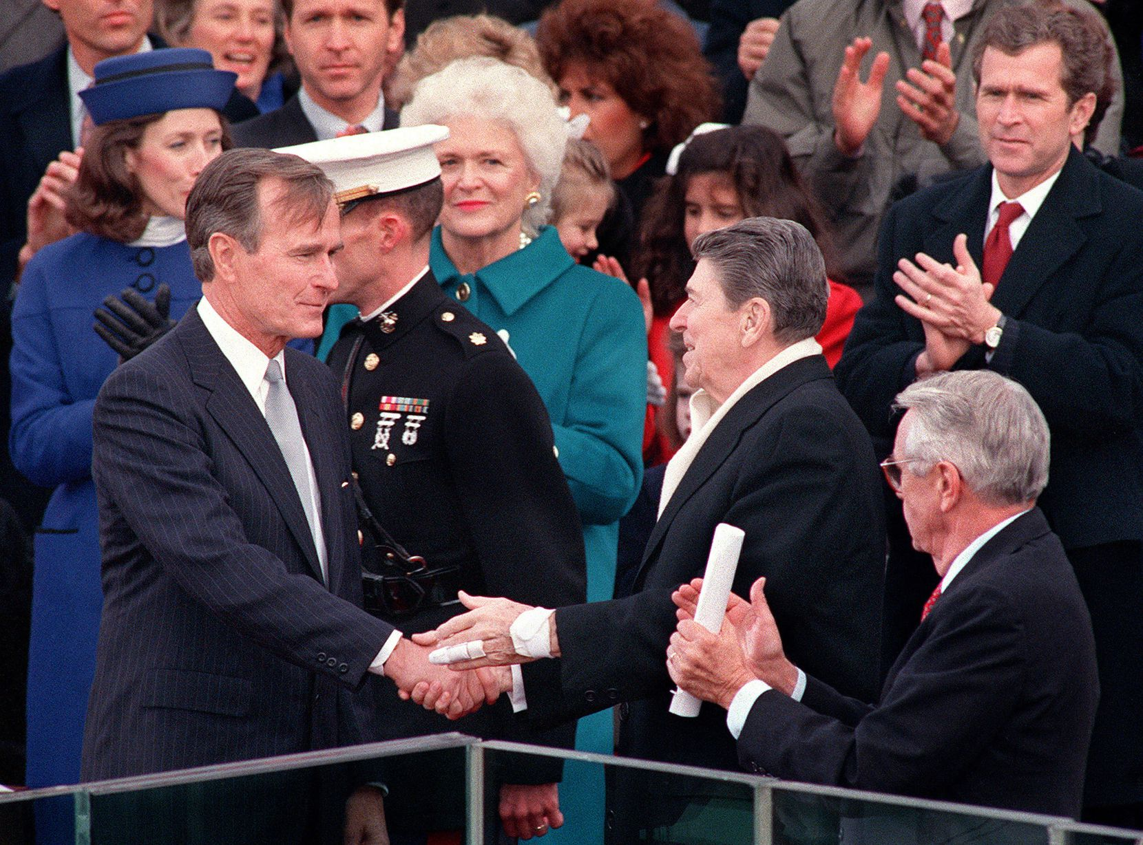 1989: Outgoing President Ronald Reagan congratulates newly inaugurated President George H.W. Bush as first lady Barbara Bush (center), George W. Bush (top right) and others applaud during the swearing-in ceremony.
